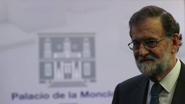 Spain's PM Rajoy leaves the conference room after delivering a statement at the Moncloa Palace in Madrid