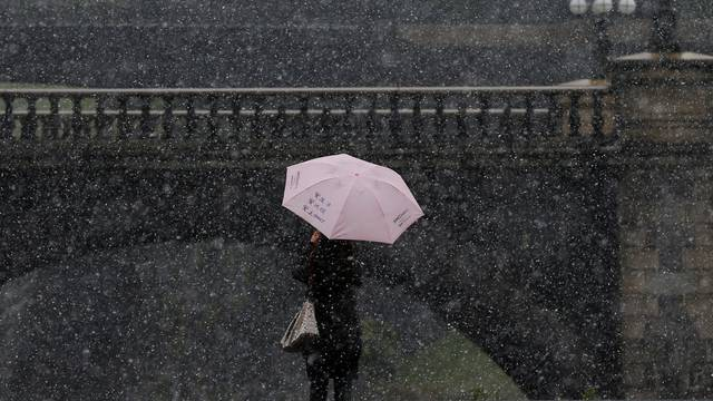 A tourist takes photos during the first November snowfall in 54 years in Tokyo
