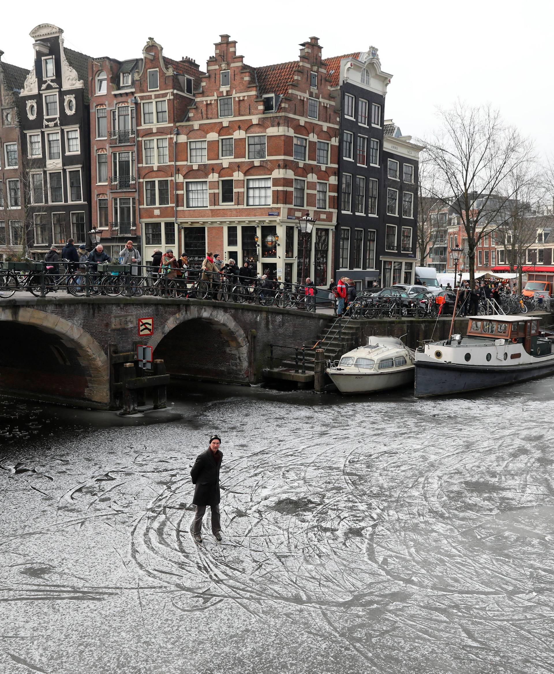 Ice skaters skate on the frozen Prinsengracht and Brouwersgracht canal during icy weather in Amsterdam