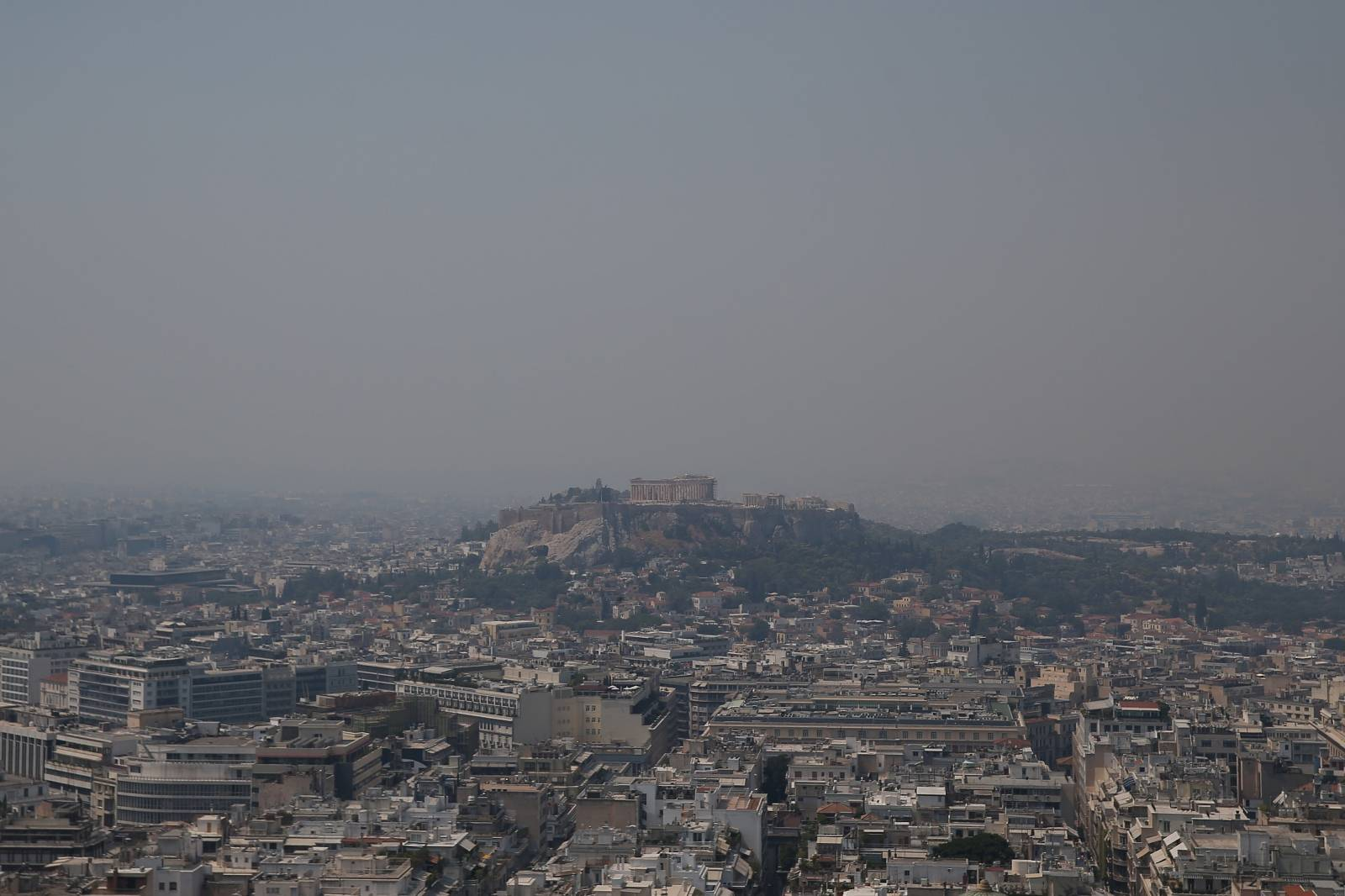 Acropolis hill with the Parthenon temple is covered with smoke from a wildfire burning the Island of Evia, in Athens