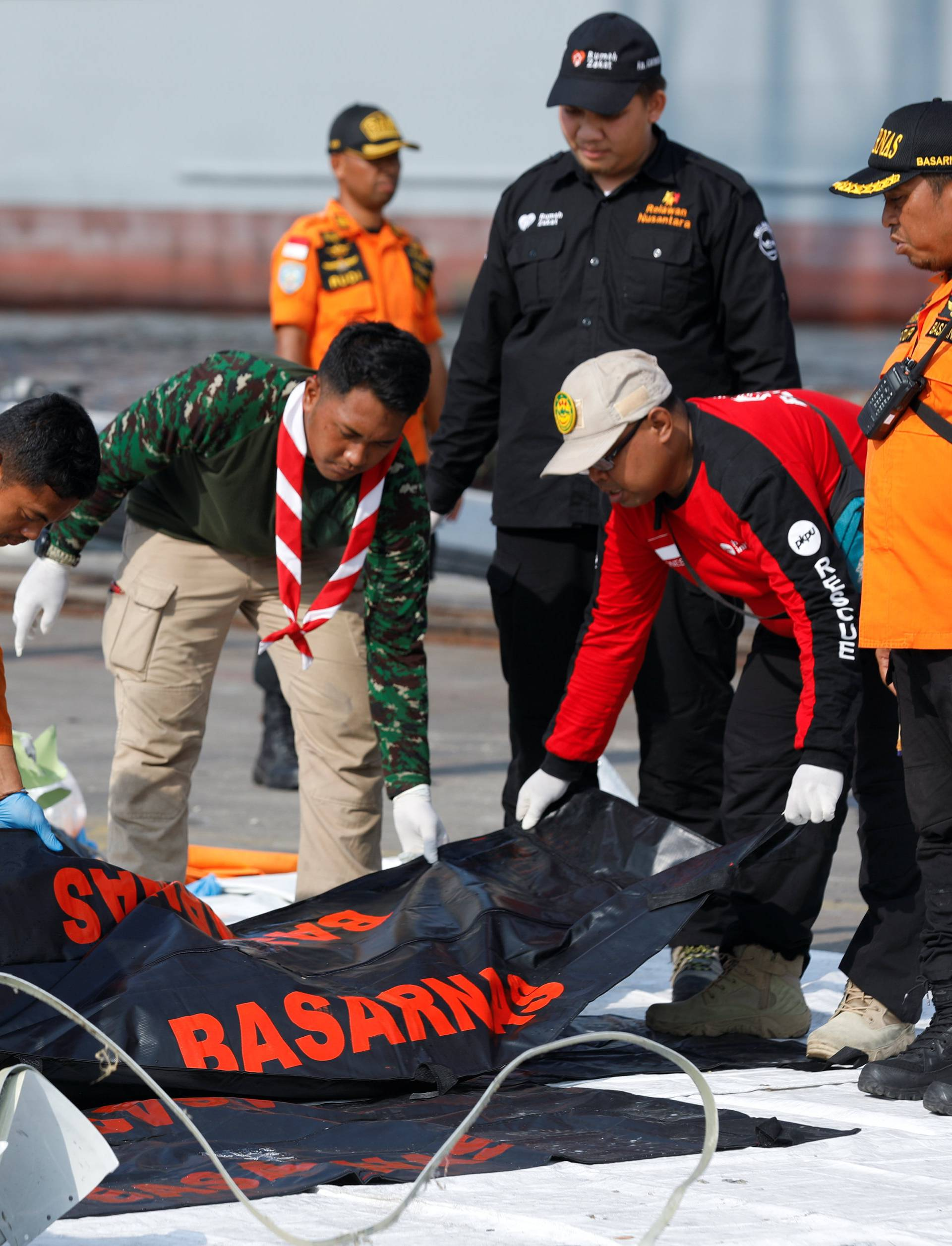Rescue workers of the crashed Lion Air flight JT610 carry body bags at the Tanjung Priok port in Jakarta
