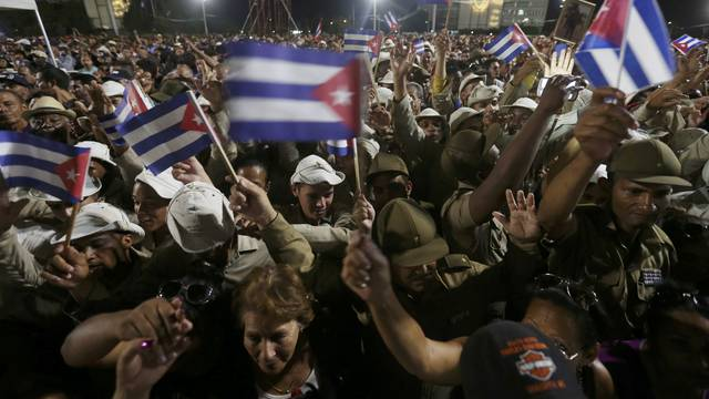 People wave Cuban flags as they attend a massive tribute to Cuba's late President Fidel Castro in Revolution Square in Havana