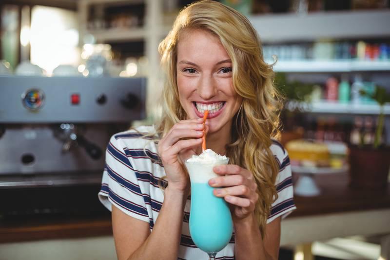 Portrait of woman drinking milkshake with a straw