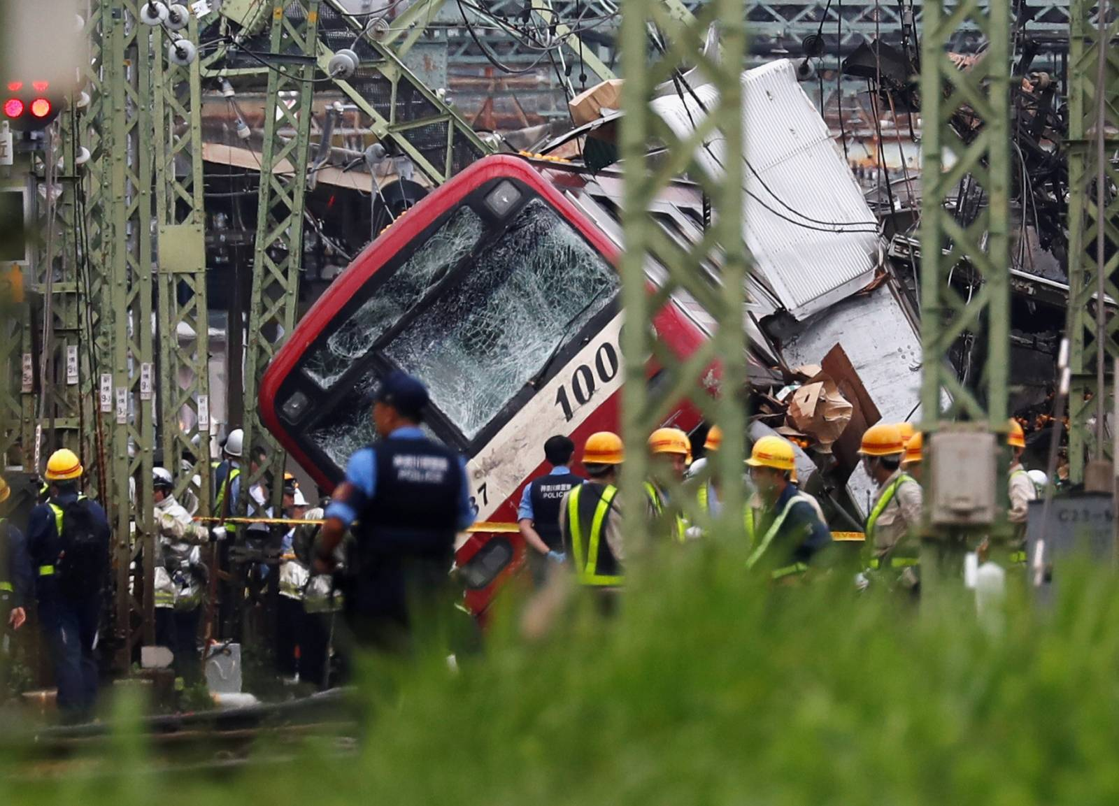 Rescue personnel and police are seen on the tracks next to a train after it derailed during a collision with a truck in Yokohama