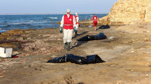 Libyan Red Crescent workers are seen near bags containing bodies of migrants, who died after their wooden boat capsized, in Khoms