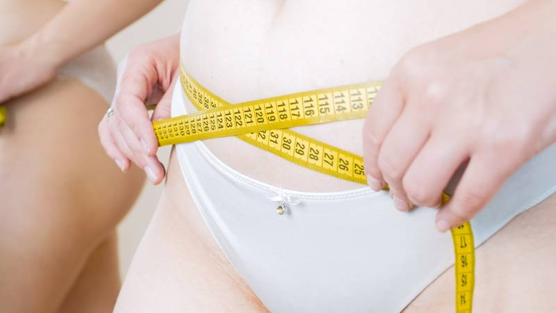 Young woman using measuring tape to measure her waist at mirror