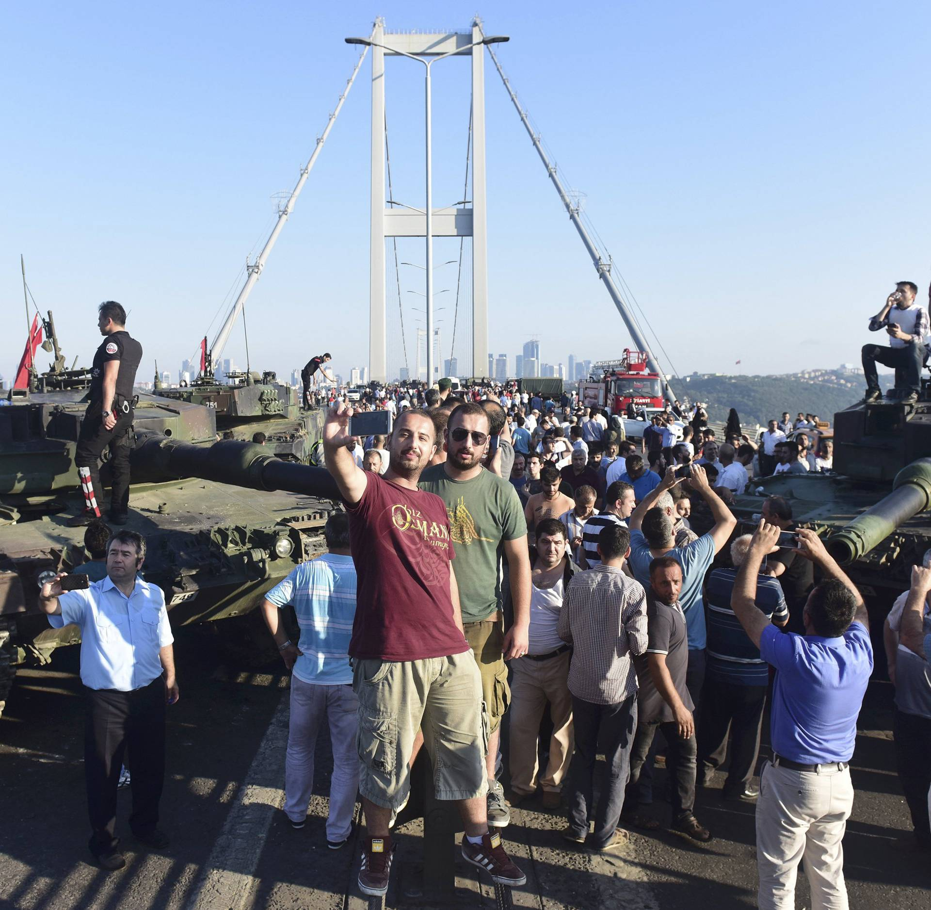People take selfies after soldiers involved in the coup surrendered on the Bosphorus Bridge in Istanbul