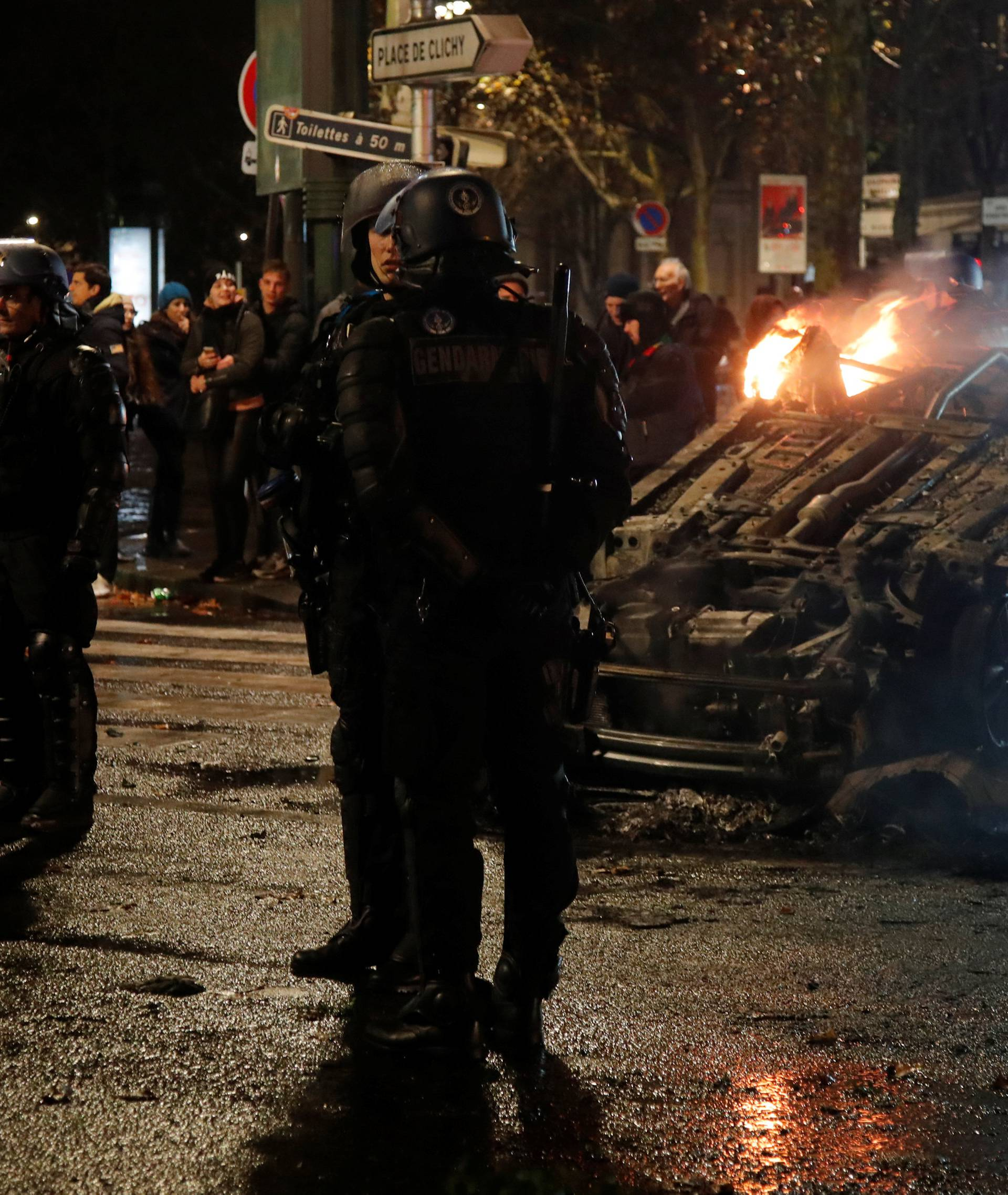 French riot police stand near an overturned burning car on avenue Kleber after clashes with protesters wearing yellow vests, a symbol of a French drivers' protest against higher diesel taxes, in Paris