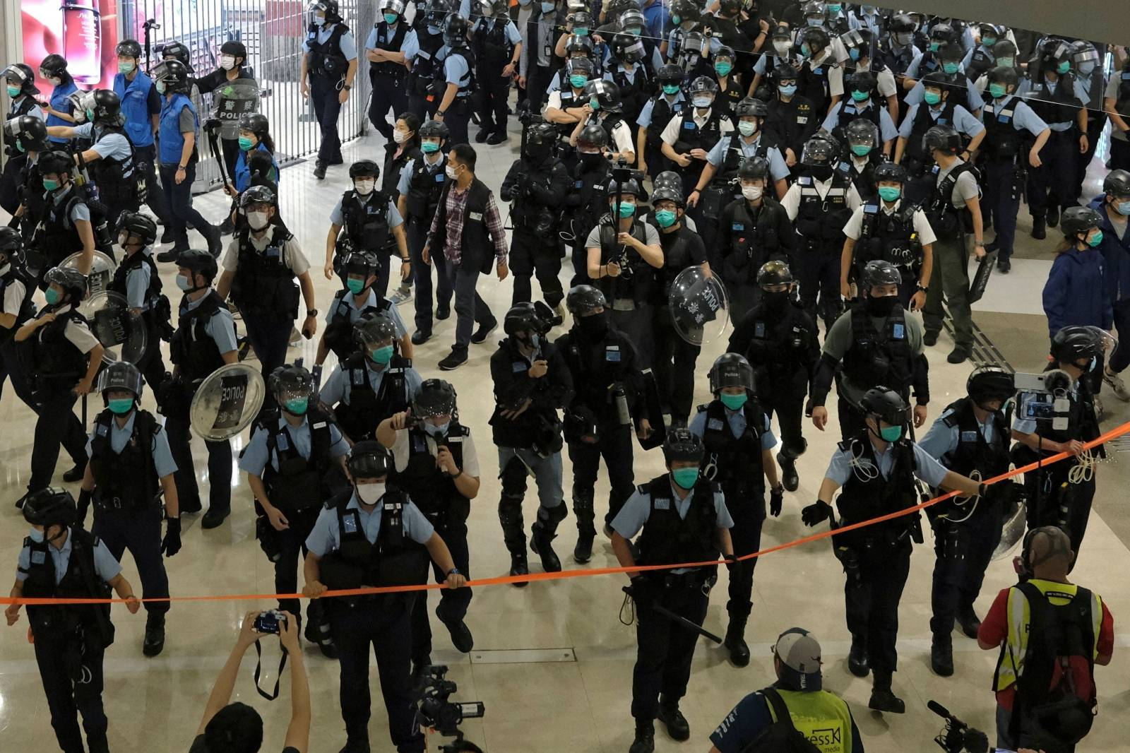 Police officers wearing face masks to avoid the spread of the coronavirus disease (COVID-19) disperse anti-government protesters from a shopping mall during a rally in Hong Kong