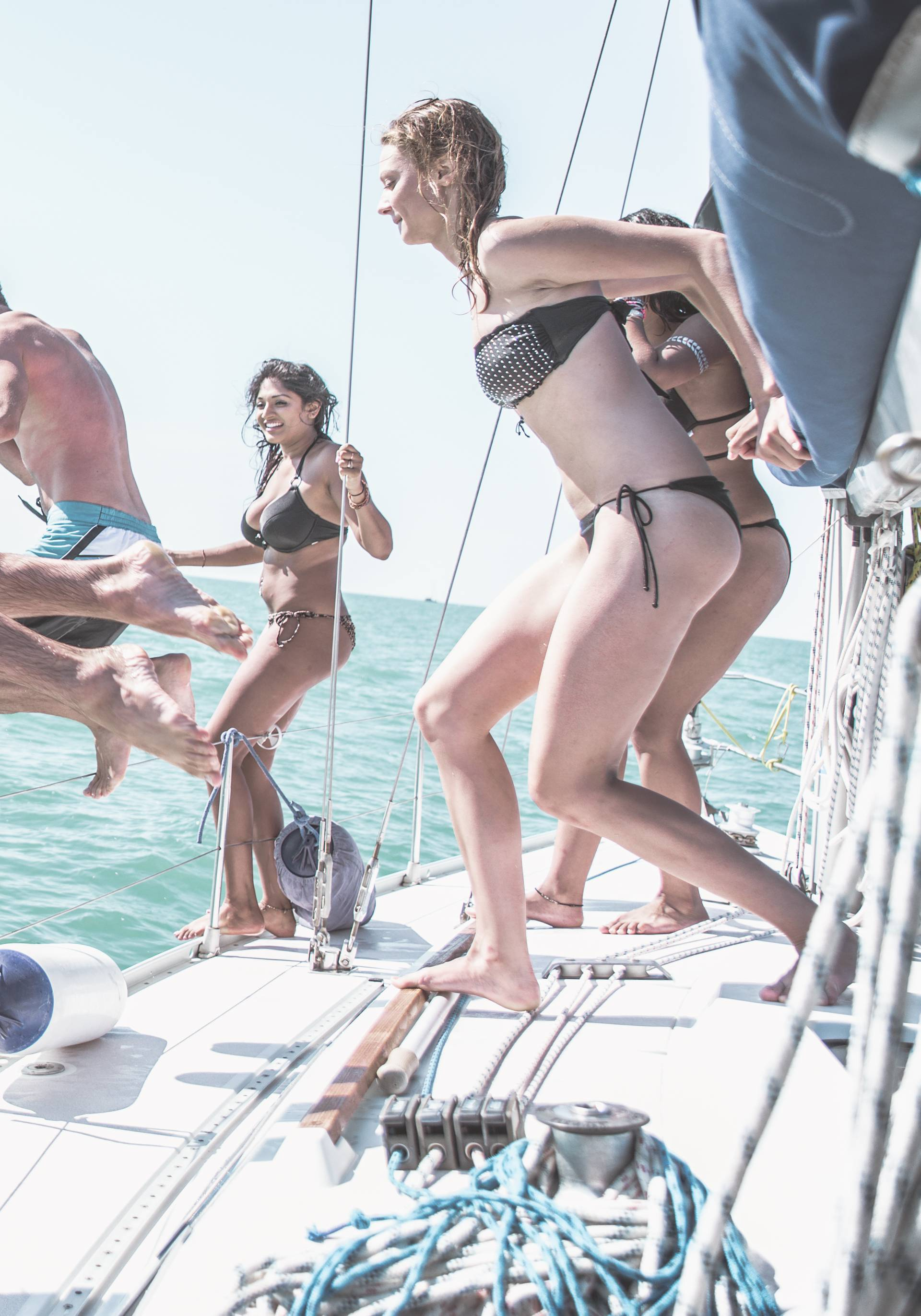 Friends jumping in the water from the boat