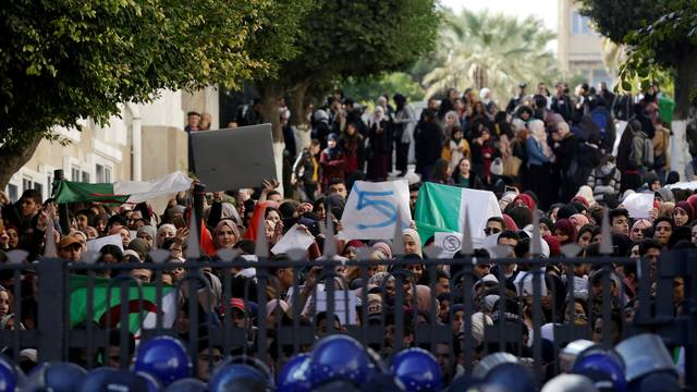Police block a university's gate while students protest inside the campus against President Abdelaziz Bouteflika's plan to extend his 20-year rule by seeking a fifth term in Algiers