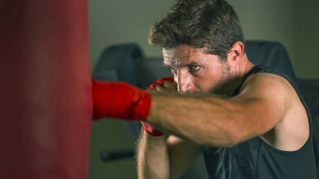 lifestyle gym portrait of young attractive and fierce looking man training boxing at fitness club doing heavy bag punching workout with wrist wraps in badass fighter look