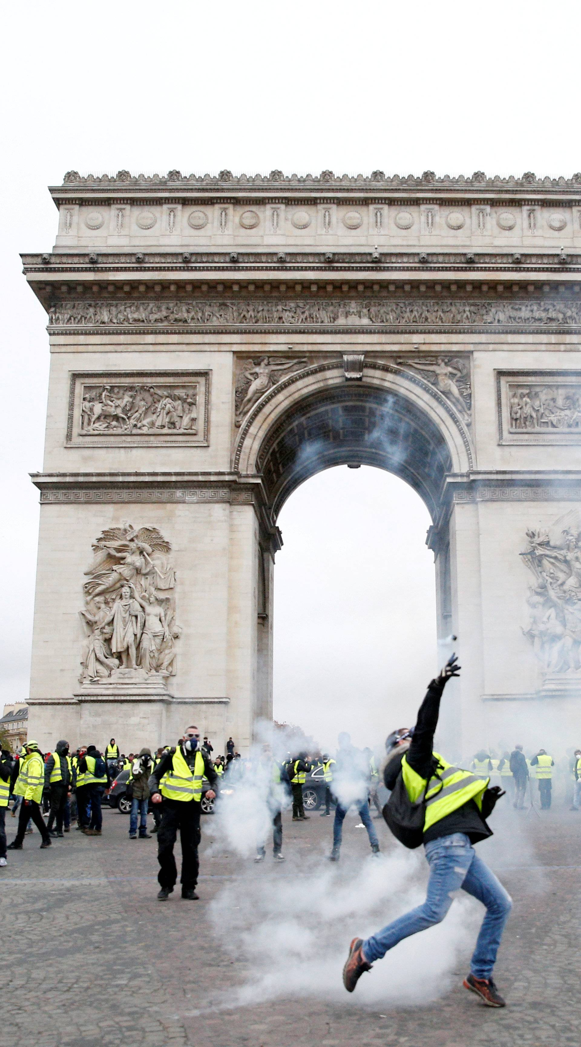 Tear gas floats in the air near the Arc de Triomphe as protesters wearing yellow vests, a symbol of a French drivers' protest against higher diesel taxes, demonstrate in Paris