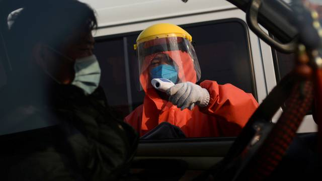 FILE PHOTO: Worker in protective suit checks temperature of a truck driver entering the Xinfadi wholesale market, as the country is hit by an outbreak of the novel coronavirus disease (COVID-19), in Beijing