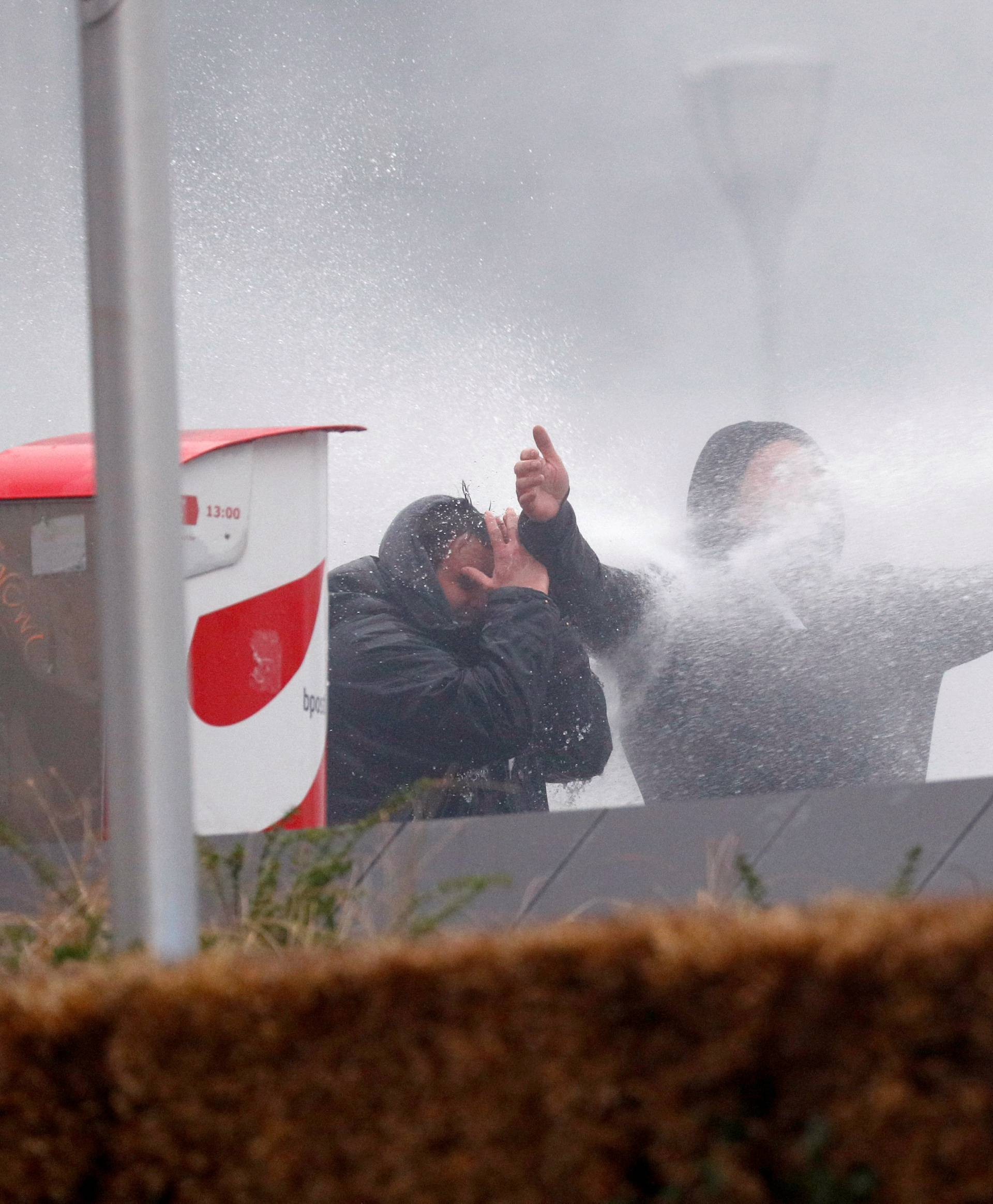 Far-right supporters are sprayed with a water cannon during a protest against Marrakesh Migration Pact in Brussels