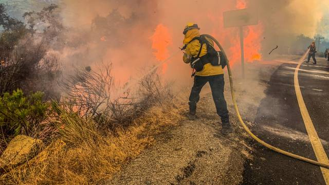 Firefighters work to extinguish a fire in Alpine, California