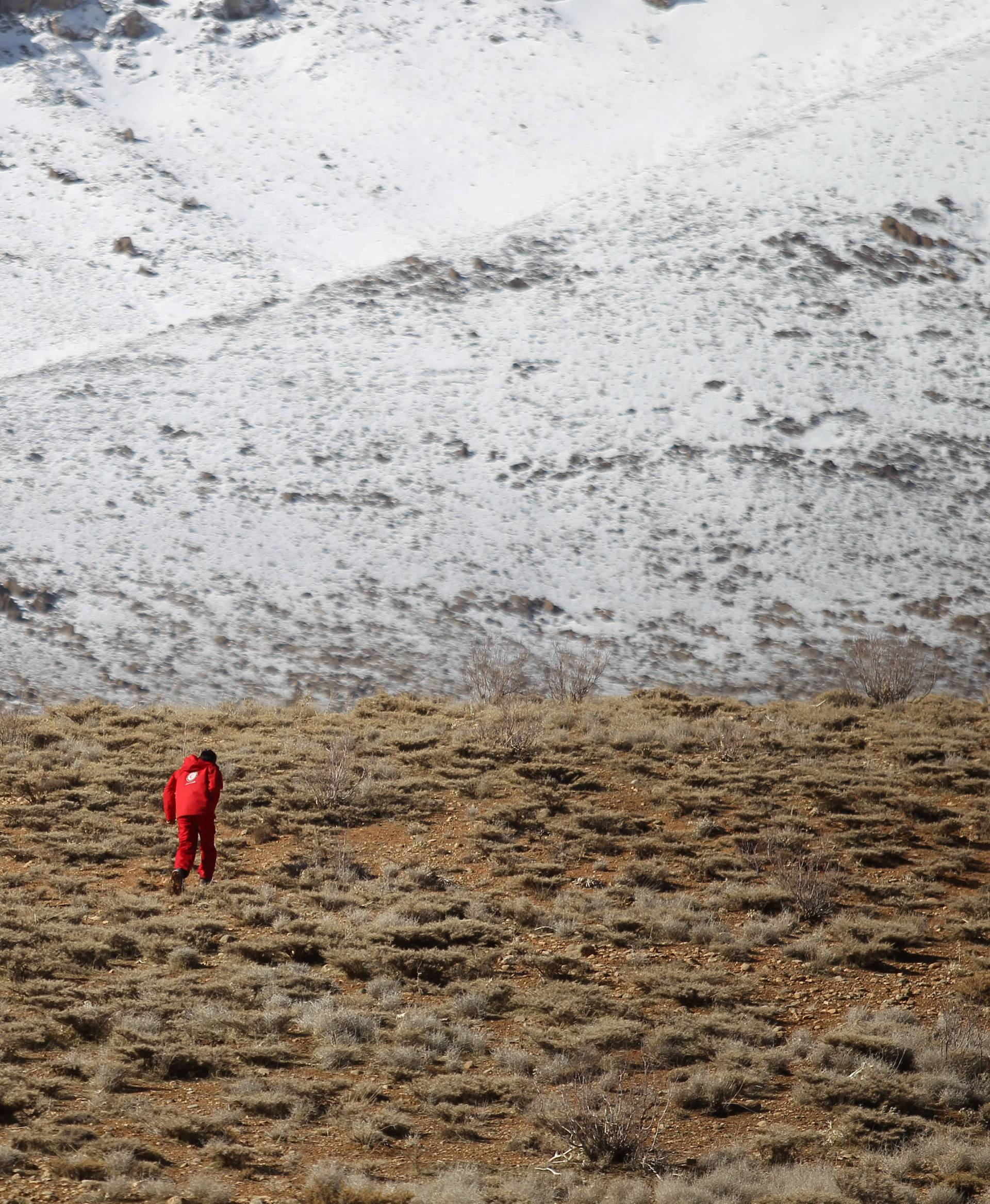 Members of emergency and rescue team search for the plane that crashed in a mountainous area of central Iran