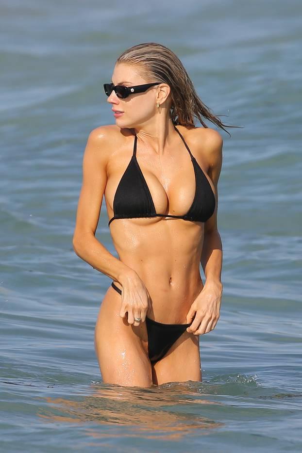 Model Charlotte McKinney wears a black string bikini as she hits the beach in Miami