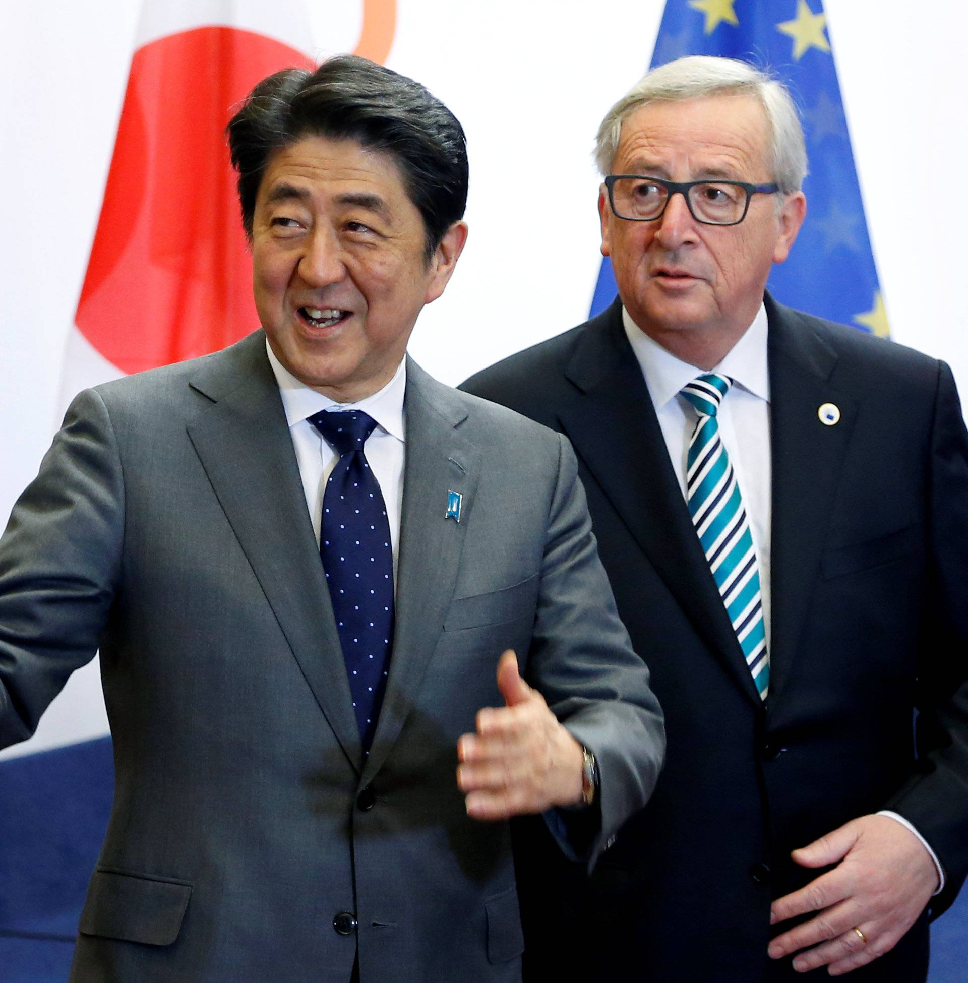 Japan's Prime Minister Shinzo Abe gestures beside European Commission President Jean-Claude Juncker before a working dinner at the EU Council in Brussels
