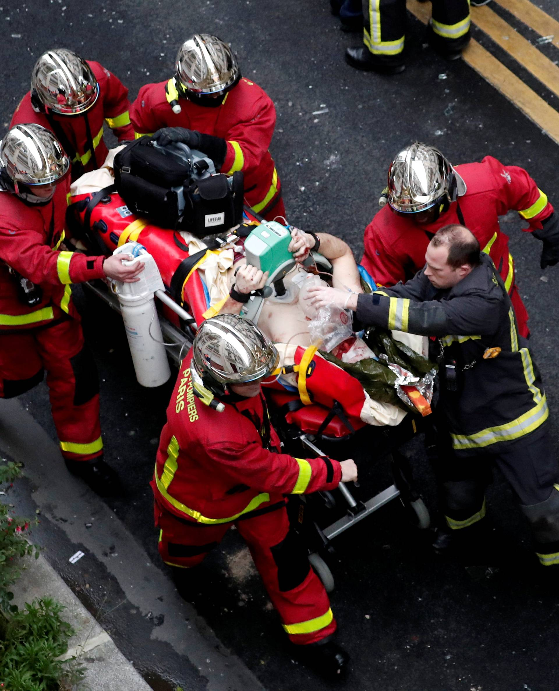 Firemen wheel a stretcher carrying a man injured in an explosion in a bakery shop in the 9th District in Paris