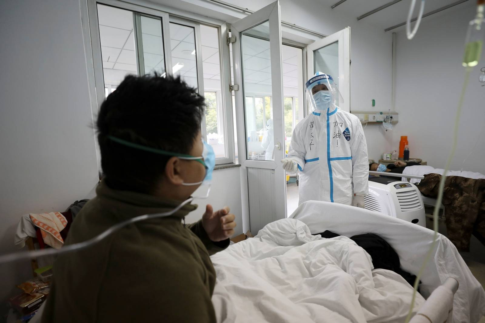 Medical worker in protective suit interacts with a patient inside an isolated ward at Jinyintan Hospital in Wuhan