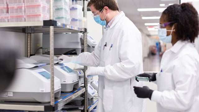 A researcher works in a lab run by Moderna