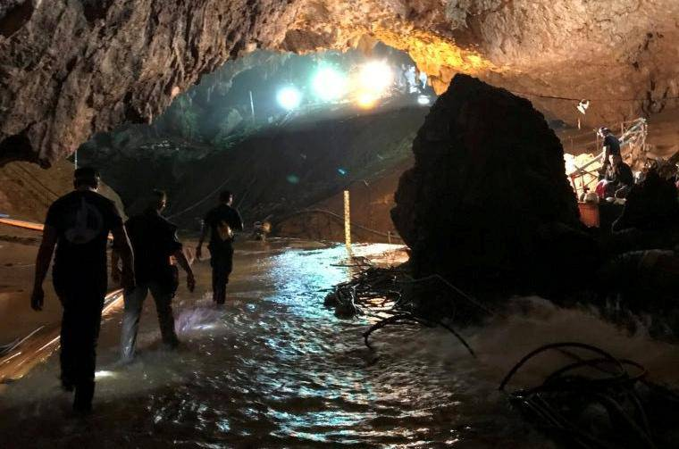 Rescue personnel walk in a cave at the Tham Luang cave complex during a mission to evacuate the remaining members of a soccer team trapped inside, in Chiang Rai