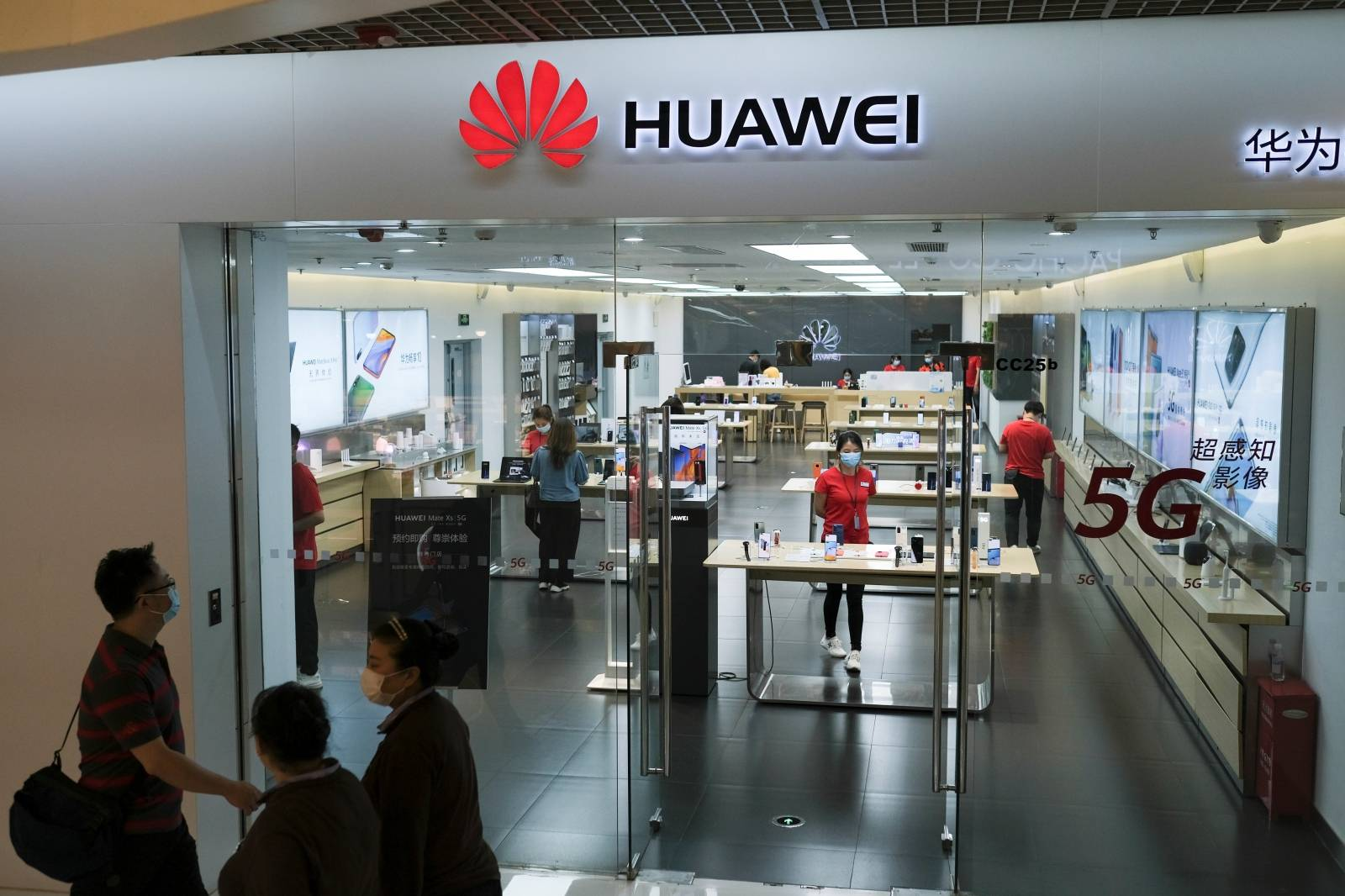 People wearing face masks walk past a?Huawei?store at a shopping mall, following an outbreak of the coronavirus disease (COVID-19), in Beijing