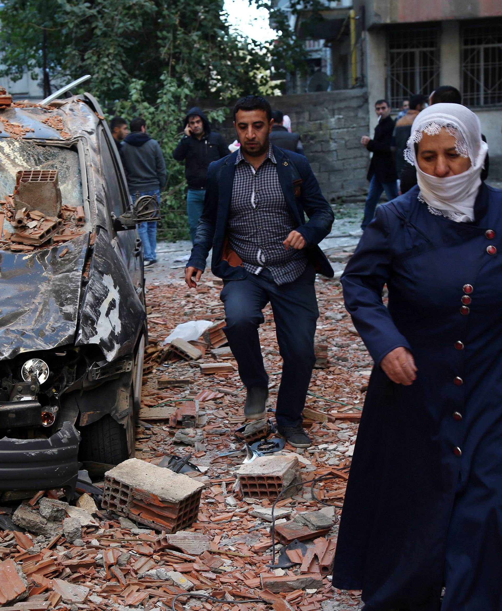 People walk past a damaged car after a blast in the Kurdish-dominated southeastern city of Diyarbakir