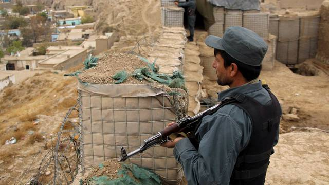 Afghan police officers keep watch at their forward base on the outskirts of Kunduz province