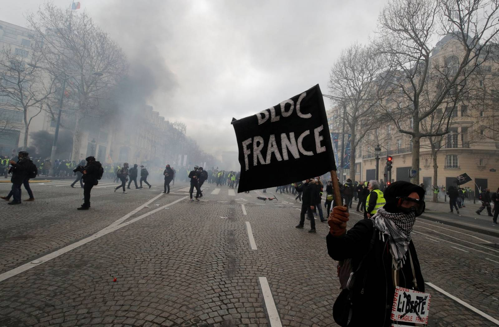 """A protester holds a flag during a demonstration by the """"yellow vests"""" movement in Paris"""