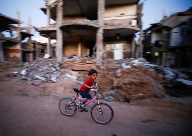 A boy rides his bicycle near the rubble of a house which was destroyed by Israeli air strikes during the Israel-Hamas fighting, in Gaza Strip