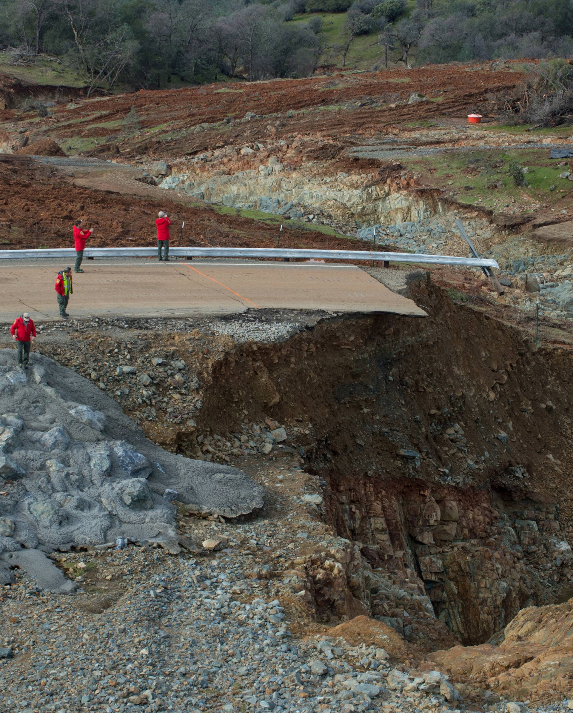 Handout photo of California Department of Water Resources crews inspect and evaluate the erosion just below the Lake Oroville Emergency Spillway site after lake levels receded, in Oroville