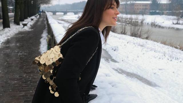 Zlatna retro torbica kao stilsko osvježenje uz crni maksi kaput