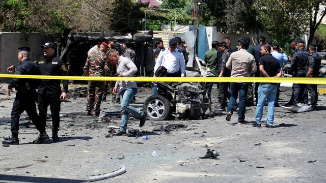 Iraqi security forces inspect the site of a car bomb attack in Baghdad