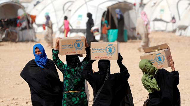 FILE PHOTO: People displaced from fightings between the Syrian Democratic Forces and Islamic State militants carry boxes of food aid given by UN's World Food Programme at a refugee camp in Ain Issa