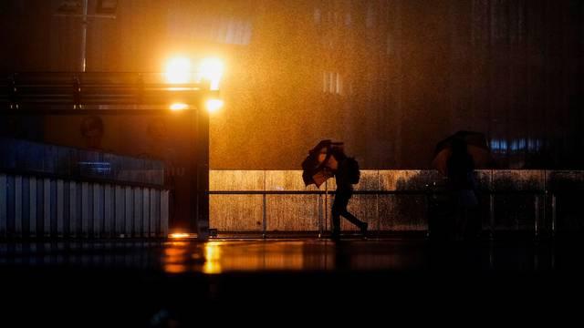 A man walks with an umbrella amid rainfall, as Typhoon Chanthu approaches, in Shanghai