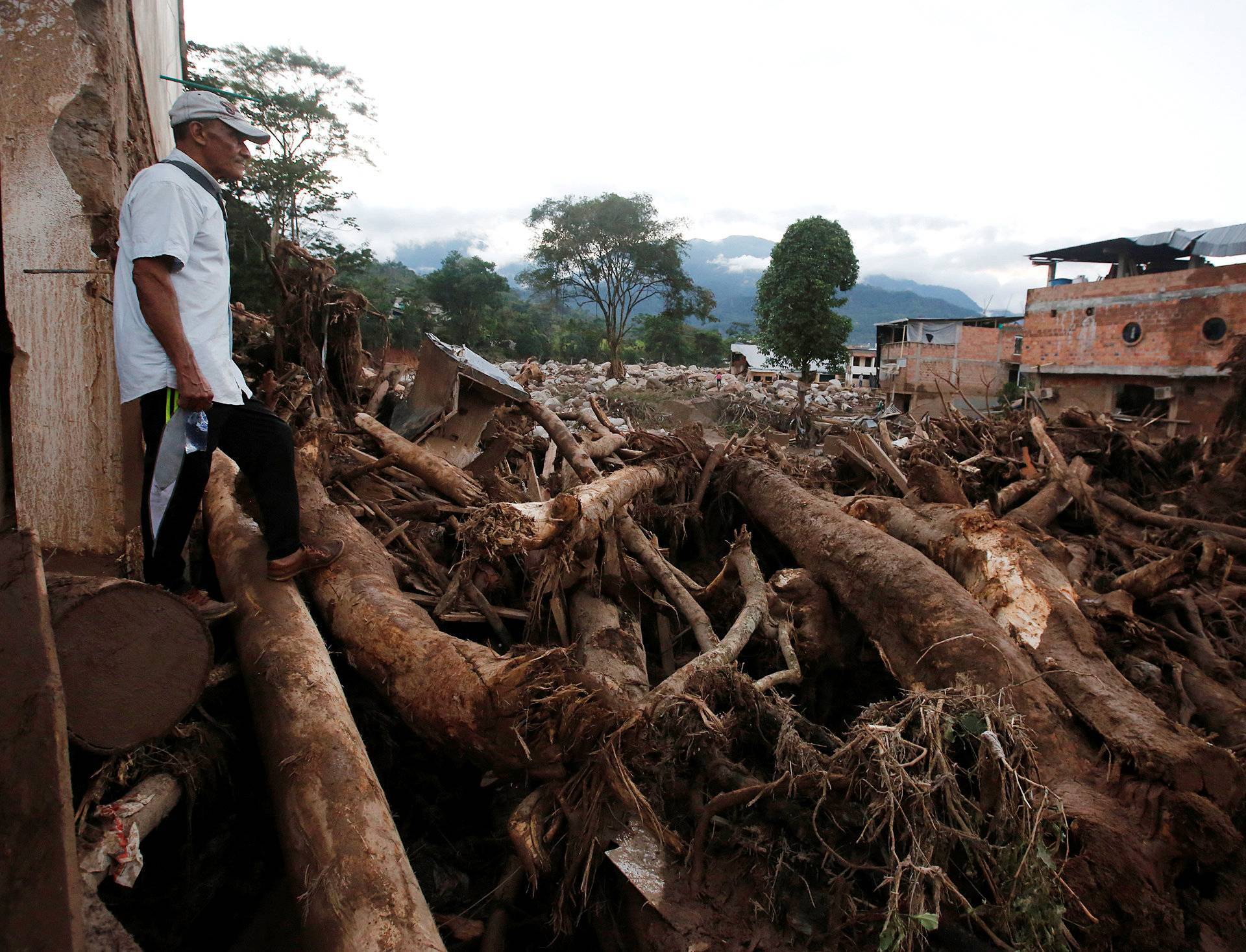 A man looks at a destroyed area after heavy rains caused several rivers to overflow, pushing sediment and rocks into buildings and roads in Mocoa