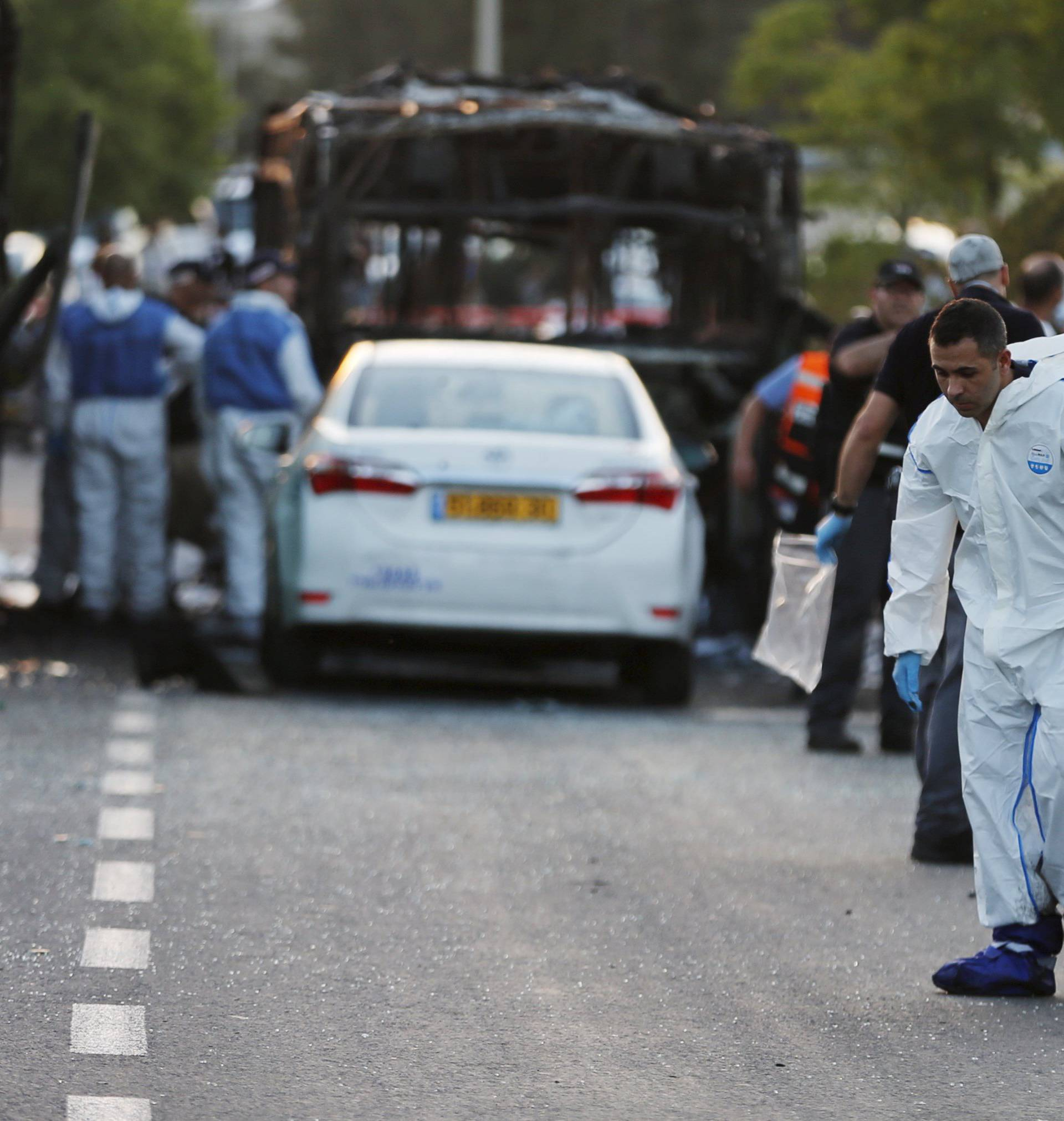 An Israeli police forensic expert works at the scene after a blast on a bus in Jerusalem