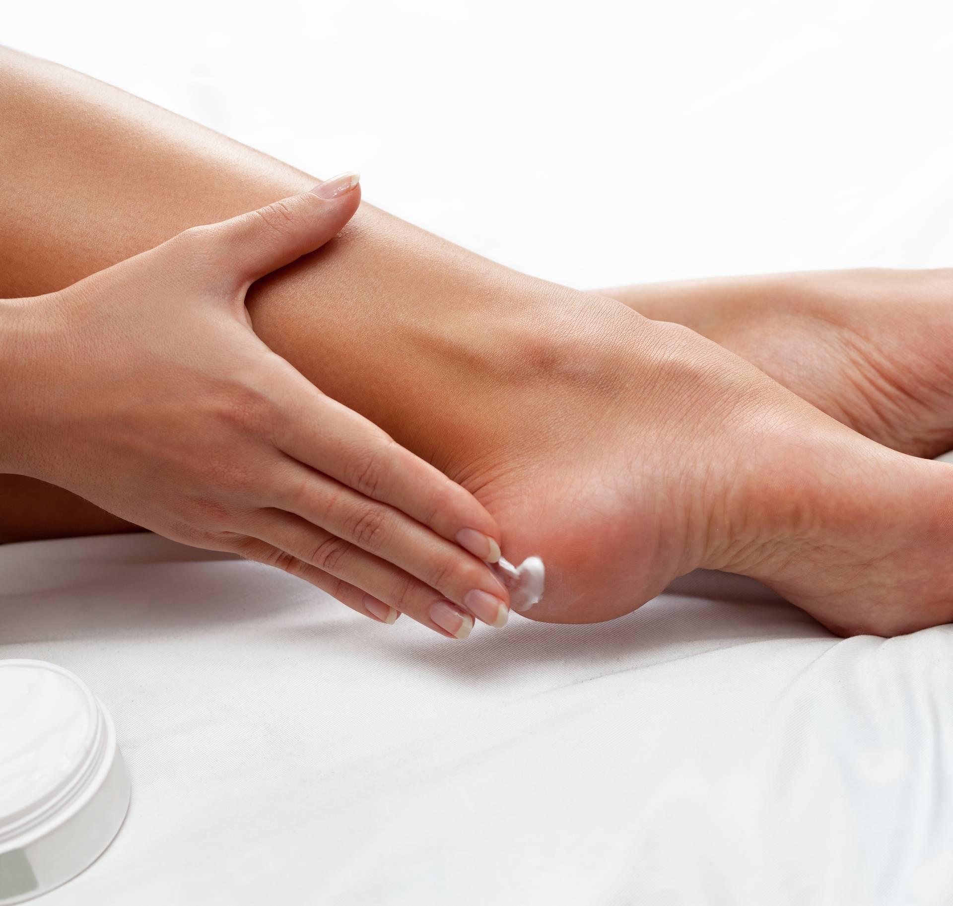 applying cream on feet