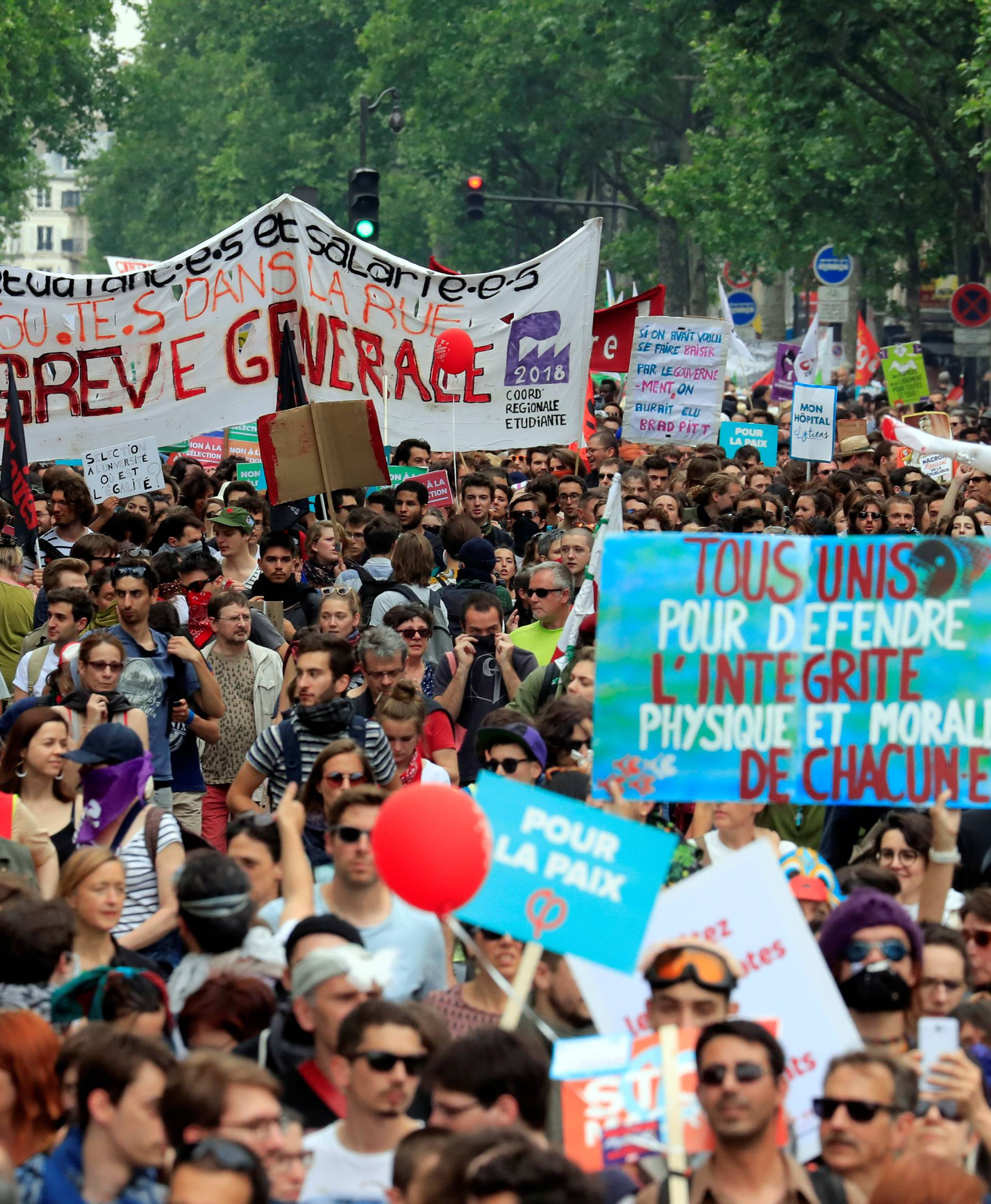 """Protesters hold placards during a demonstration by French unions and France Insoumise"""" (France Unbowed) political party to protest against government reforms, in Paris"""