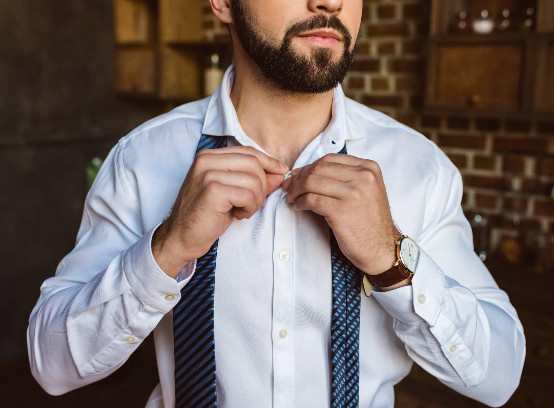 businessman fastening buttons on shirt