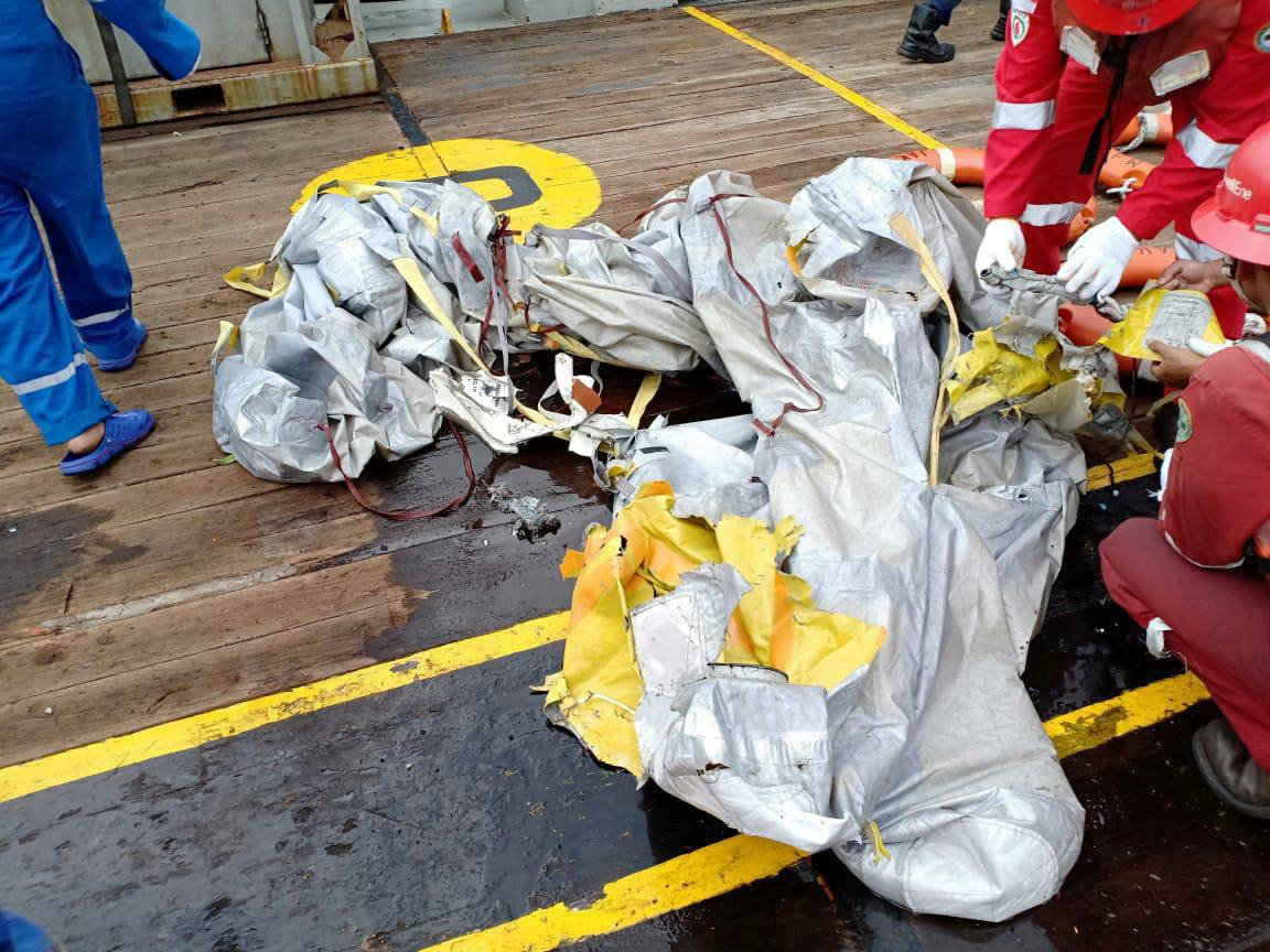 Workers of PT Pertamina examine recovered debris from what is believed to be the crashed Lion Air flight JT610, onboard Prabu ship owned by PT Pertamina off the shore of Karawang regency