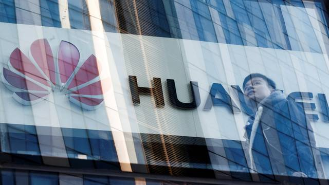 A man walks past a Huawei shop in Beijing