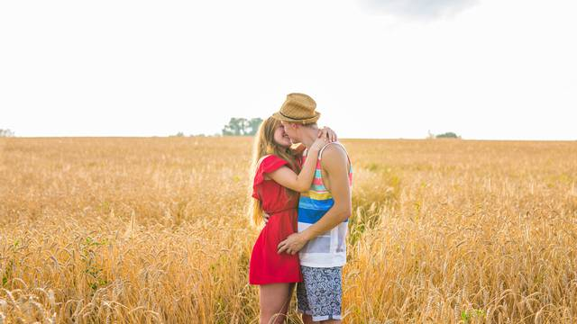 Stunning sensual portrait of young stylish fashion man and woman posing in field