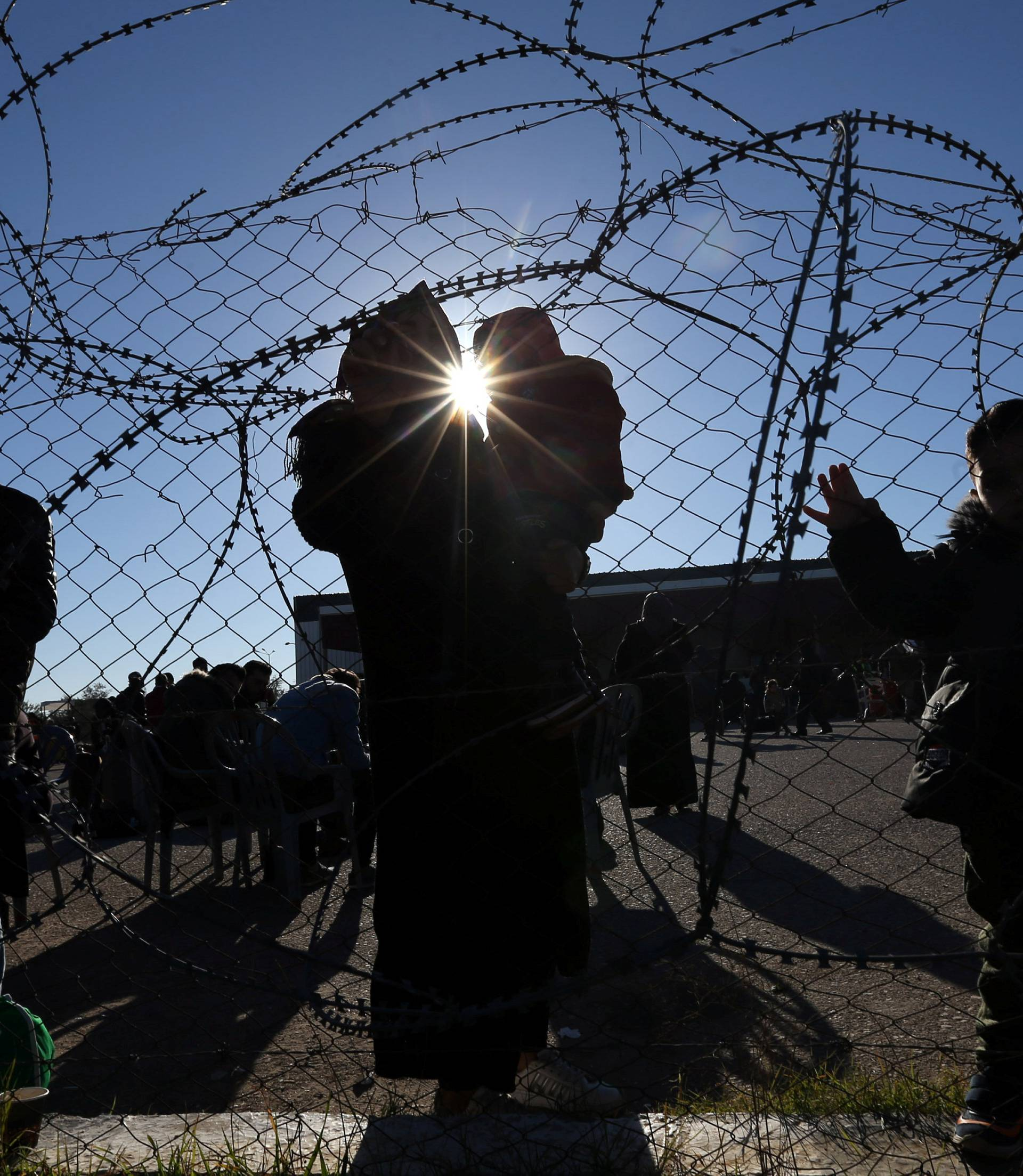Palestinians stand by a fence as they wait for travel permits to leave Gaza through Rafah border crossing with Egypt, in Rafah, in the southern Gaza Strip