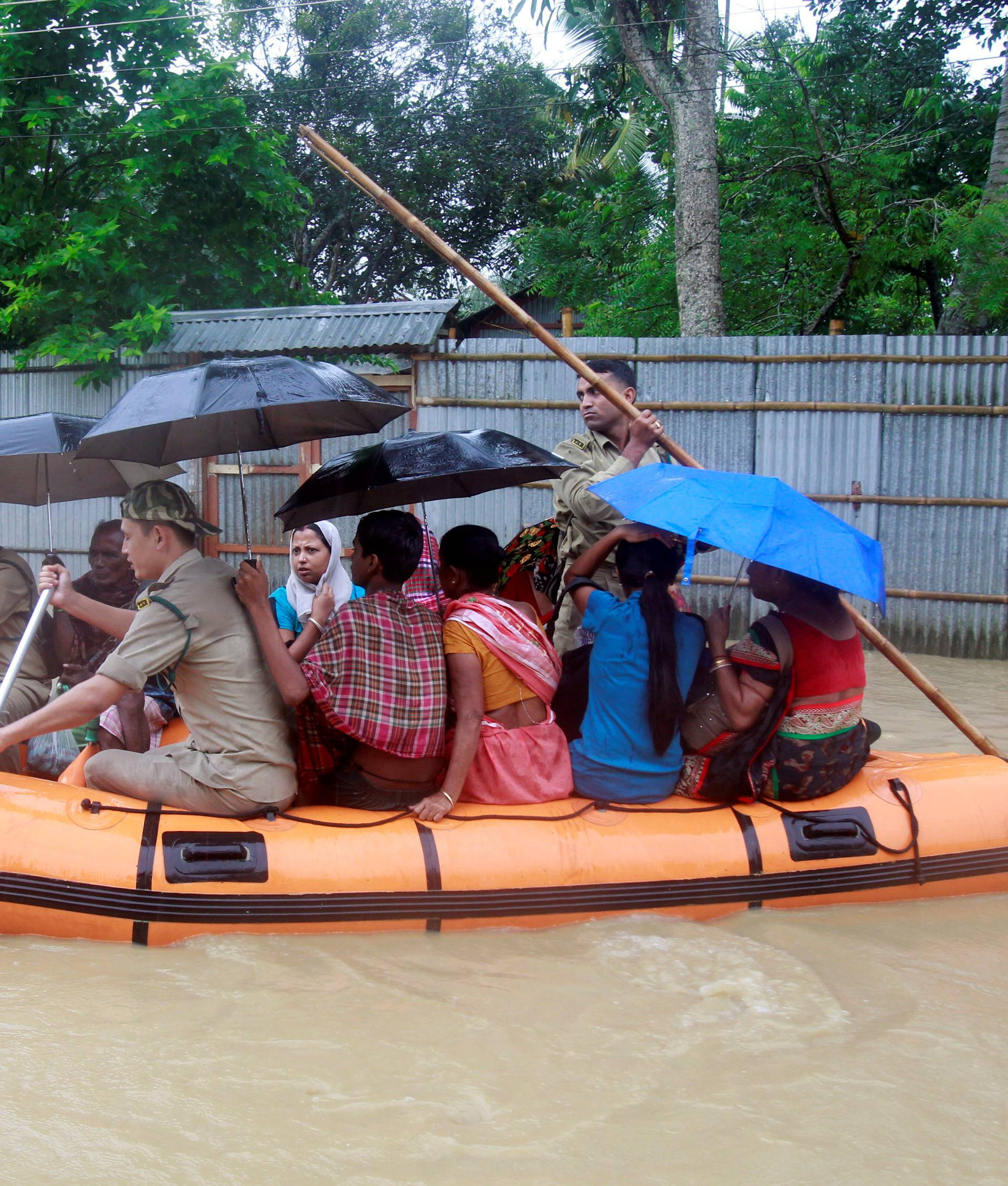 Members of Tripura State Rifles evacuate people from a flooded area after heavy rains in Baldakhal village on the outskirt of Agartala