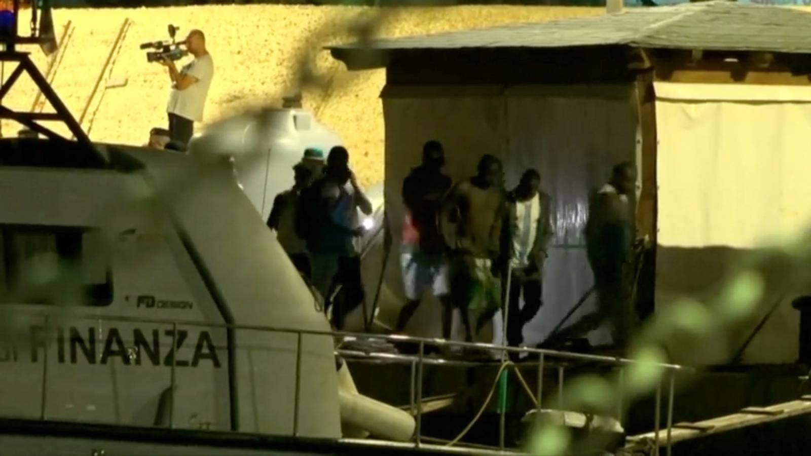 Migrants disembark a rescue boat in the port of Lampedusa