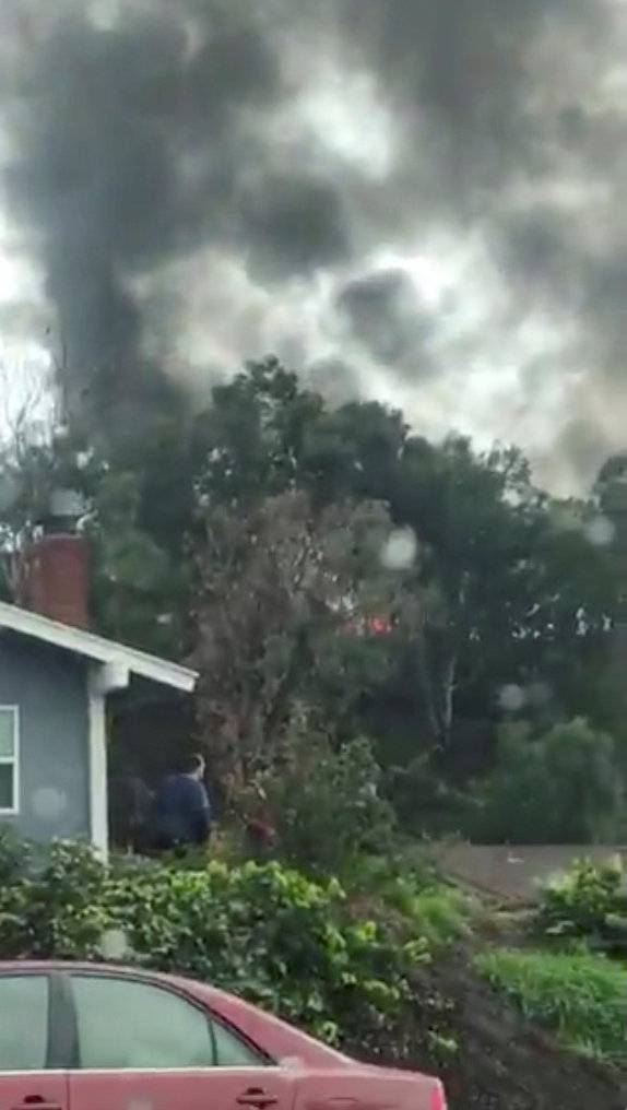 People look in the direction of smoke billowing after a plane crashed into a house in a residential neighborhood in Yorba Linda, California