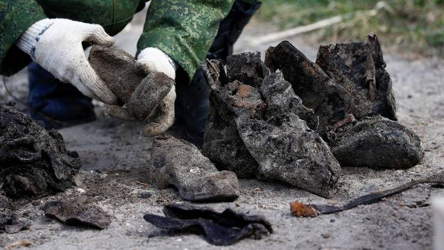 """A soldier from a special """"search battalion"""" of Belarus Defence Ministry takes part in the exhumation of a mass grave containing the remains of about 730 prisoners of a former Jewish ghetto, discovered at a construction site in the centre of Brest"""